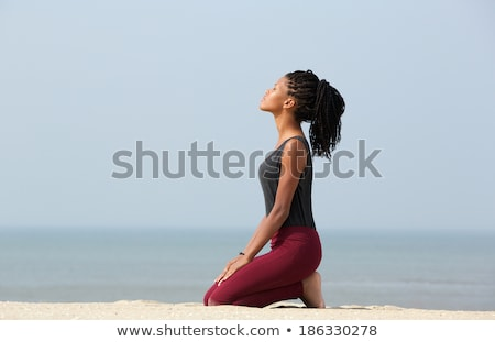 side view of beautiful young african american woman sitting at poolside in her backyard stock photo © wavebreak_media