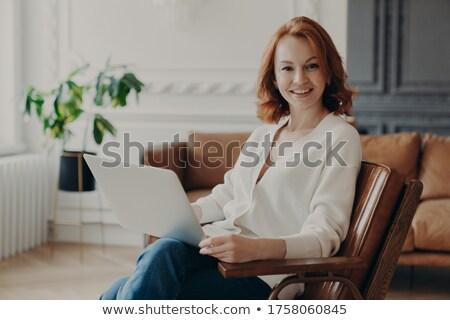 Photo of glad European woman freelancer satisfied with remote job, works freelance on laptop compute Stock photo © vkstudio