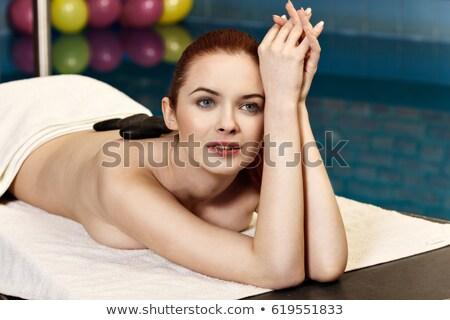 Redhead woman with black stones treatment Stock photo © lunamarina
