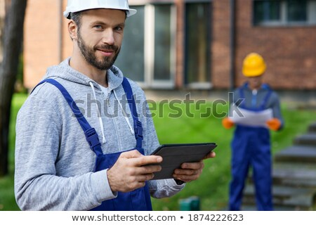smilling handyman using pc tablet computer while working stock photo © deandrobot