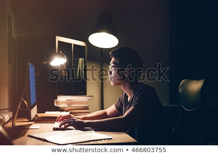 Thoughtful asian man using computer at table in dark room Stock photo © deandrobot