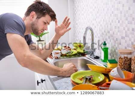 Sad Man Looking At Dirty Utensils Stock photo © AndreyPopov