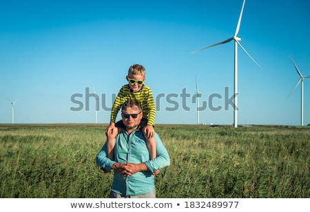 Father carrying son on shoulders and waving their arms like a windmill Сток-фото © galitskaya