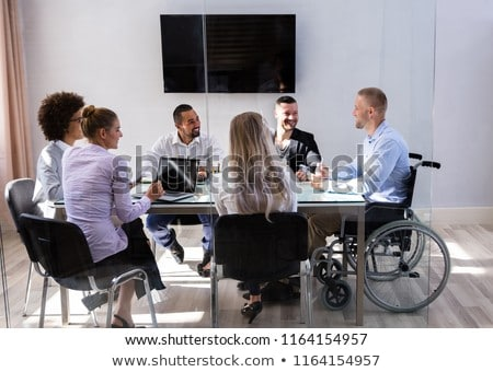 disabled manager sitting with his colleagues stock photo © andreypopov