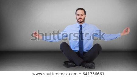 Business man meditating against grey wall Stock photo © wavebreak_media