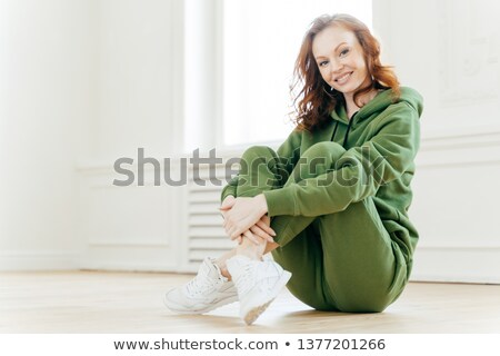 Image of satisfied refreshed young woman with foxy hair, keeps legs crossed, wears tracksuit and spo Stock photo © vkstudio