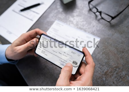 Man Taking Photo Of Cheque To Make Remote Deposit Stock photo © AndreyPopov