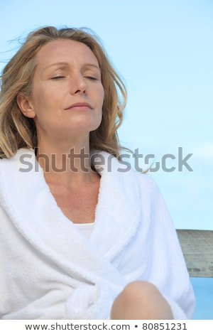 Woman relaxing in the sunshine in a towelling robe Stock photo © photography33