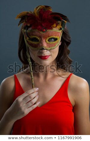 Stock photo: Woman wearing masquerade mask against black background