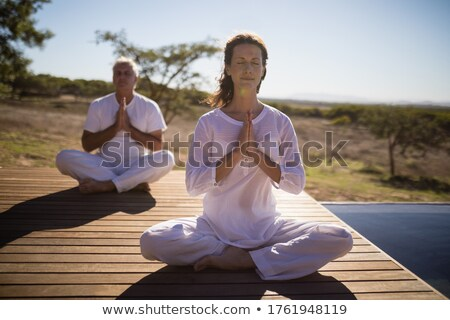 Couple practicing yoga on wooden plank Stock photo © wavebreak_media