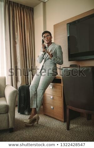женщину Постоянный номер в отеле телефон путешествия спальня Сток-фото © IS2