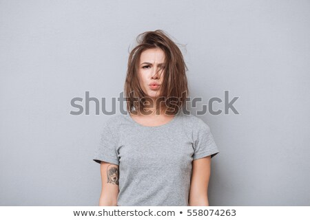 Charming young girl in a gray T-shirt on a gray background. The girl points fingers upward Stock photo © Traimak