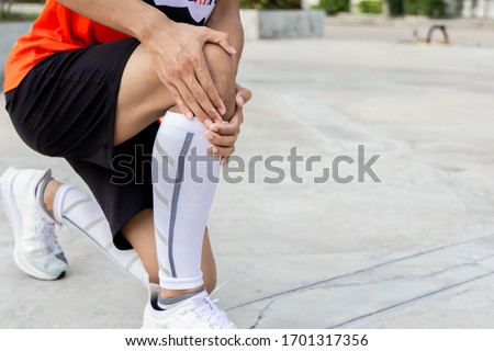 Man is holding his knee that hurts Stock photo © boggy