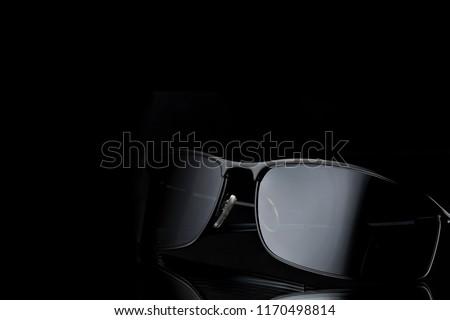 Black sunglasses on a dark background. Stock photo © artjazz