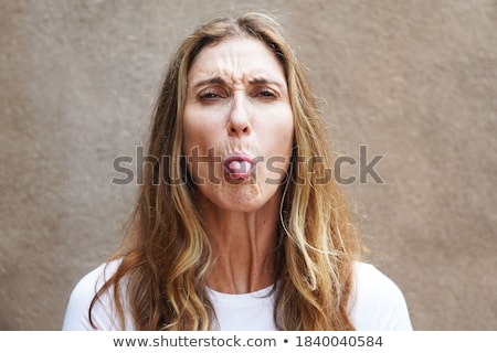 Girl sticking out her tongue against a white background Stock photo © wavebreak_media
