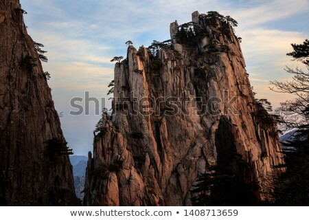 Jagged granite rock cliff edge and blue sky. Stock photo © latent