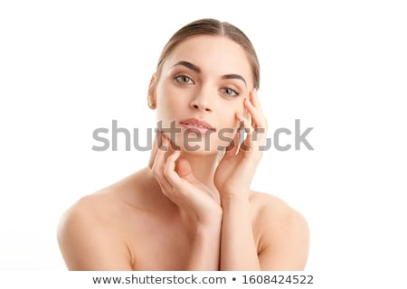 Beauty shot of a young model touching her face and looking at camera, isolated on blue Stock photo © deandrobot