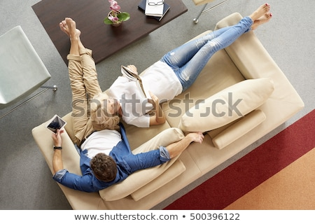 Smiling women sitting on sofa relaxing while browsing online sho Stock photo © boggy
