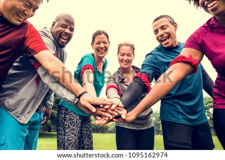 happy smiling friends stacking hands in park Stock photo © dolgachov