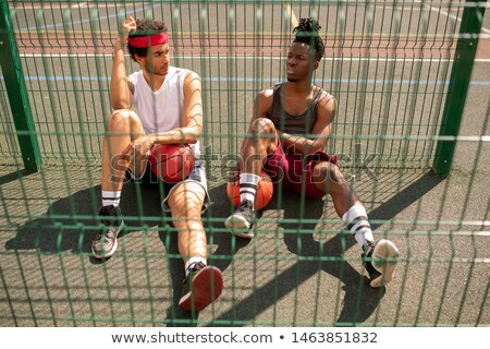 One of young intercultural basketballers telling his friend of game details Stock photo © pressmaster