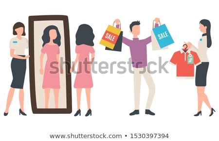 Woman standing at the clothes rack of the boutique holding two bags Stock photo © wavebreak_media