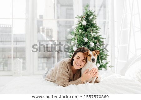 Merry lovely woman with cute dog, embraces pet and expresses love, dressed in winter sweater, pose t Stock photo © vkstudio