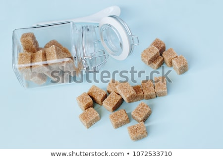 Glass jar of natural white refined sugar with cubes on light table background. Stock photo © DenisMArt