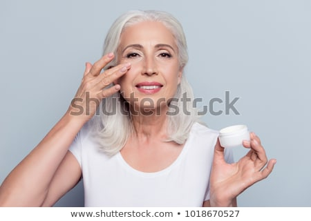 Woman rubbing moisturizer on face Stock photo © IS2