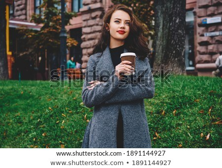 Delighted young woman dressed in autumn coat Stock photo © deandrobot