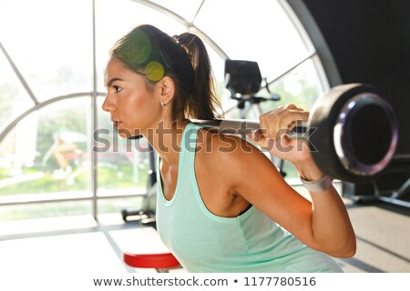 Side view of amazing sports woman doing exercise with barbell Stock photo © deandrobot