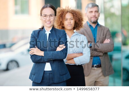 Row of young successful colleagues in formalwear with female leader in front Stock photo © pressmaster