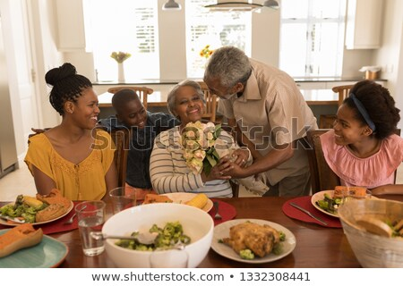 Front view of African American senior man giving a beautiful flower bouquet to his wife surrounded b Stock photo © wavebreak_media