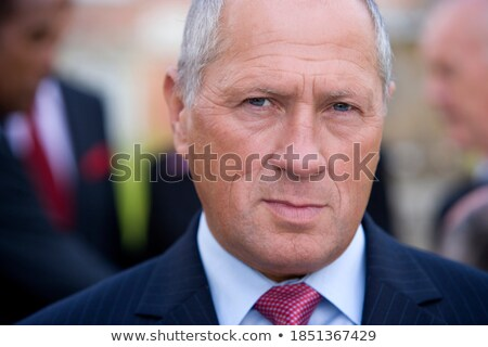Outdoor shot of happy businessman wears formal suit and tie, has stubble, looks with positive expres Stock photo © vkstudio