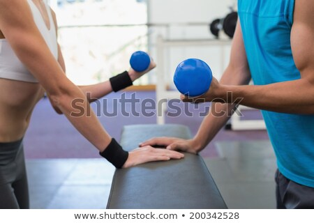 Foto stock: Mid section of a fit man lifting dumbbells