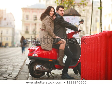 Young attractive loving couple on scooter outdoors. Looking aside. Stock photo © deandrobot
