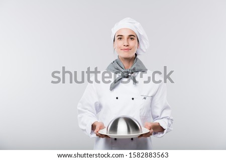 Happy young successful female chef in uniform carrying cloche with cooked meal Stock photo © pressmaster