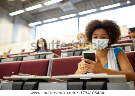 student girl with smartphones at lecture Stock photo © dolgachov