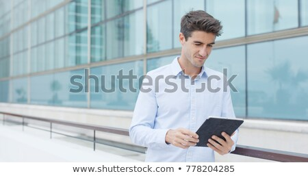Young smiling man with tablet computer on street stock photo © adamr
