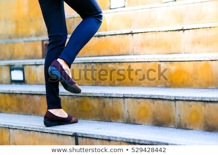 Stock photo: Old woman walks upstairs