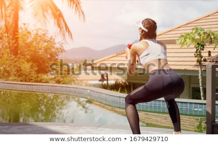 Sportswoman squatting with dumbbells on poolside Stock photo © dash