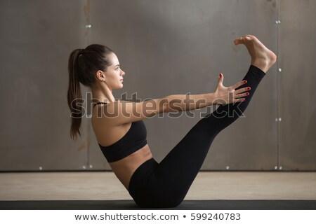 Woman doing Ashtanga Vinyasa Yoga asana Navasana - boat pose Stock photo © dmitry_rukhlenko