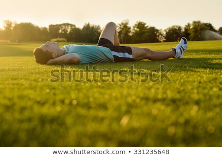 Young man lying down in the park Stock photo © wavebreak_media