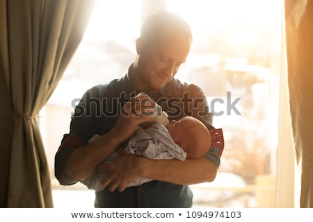 father feeding baby daughter from bottle at home Stock photo © dolgachov