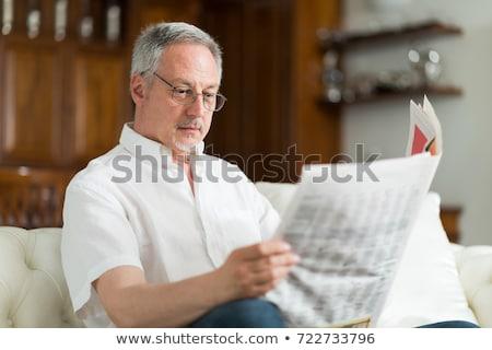 senior man reading newspaper at home stock photo © dolgachov