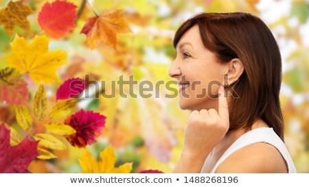 senior woman pointing to her golden earring Stock photo © dolgachov