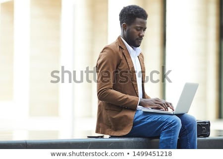 Side view of African-American man using laptop while sitting at sun lounger at beach on a sunny day. Stock photo © wavebreak_media