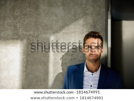 well dressed man leaning against a modern building Stock photo © photography33