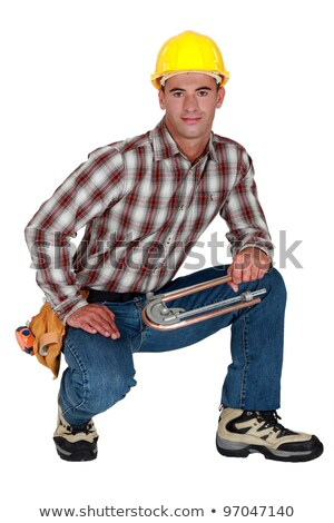 Stock photo: Tradesman holding a tube bender