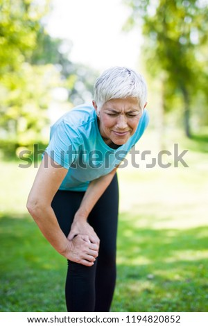 Senior sportswoman with knee pain standing in park Stock photo © boggy