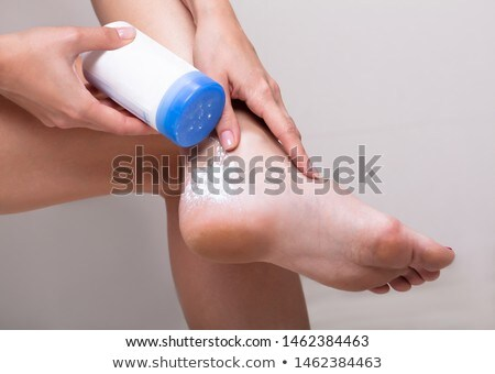 Woman Applying Powder On Her Feet Stock photo © AndreyPopov